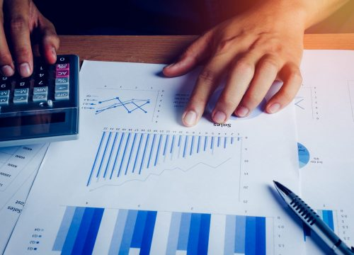 Selective focus hand asian business man is calculating finance and accounting with growth up paper chart on wood table in home office.Pen calculator graph document on desk.economy,saving,financial.